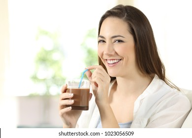 Happy woman drinking cocoa shake looking at camera sitting on a couch in the living room at home