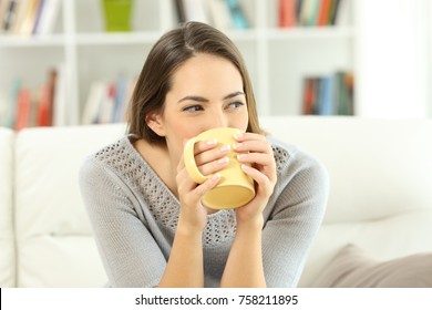 Happy woman drinking coffee looking at side sitting on a sofa at home