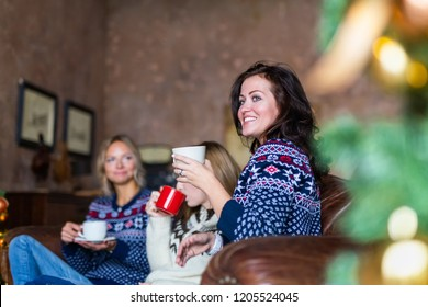 Happy woman drinking coffee while sitting on a couch chatting with her friends on New Year's eve