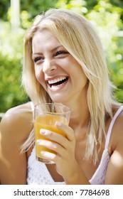 happy woman drinking her morning orange juice in her garden