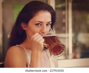 Happy woman drinking light lager beer in pab and looking. Vintage portrait