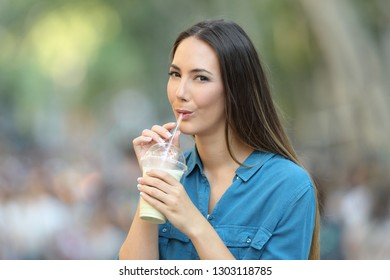 Happy woman drinking milk shake with a straw in the street looking at you