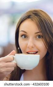 Happy woman drinks coffee