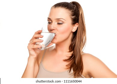 happy woman drinks water from a glass on white background