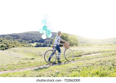 Happy Woman driving by bike with balloons
