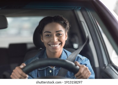 Happy woman driving car and smiling going to work or on road trip. Cute young positive happy african american female with safety belt holds steering wheel looking through the windshield, empty space