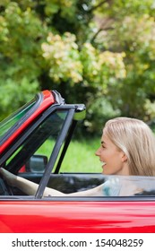 Happy woman driving red cabriolet on a sunny day