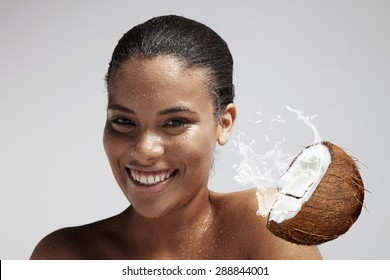 happy woman with a drops of a coconut milk on her skin