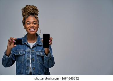 Happy woman in earrings holding a phone and a credit card in hands.