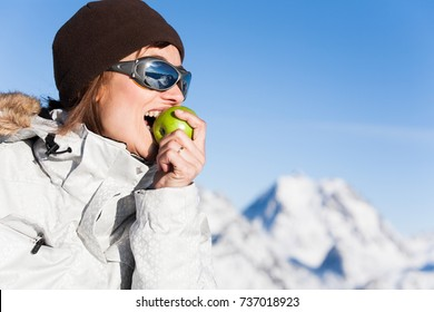 happy woman eating an apple in the snowy summits
