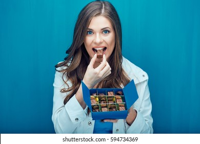 Happy woman eating chocolate candy. Portrait on blue background.