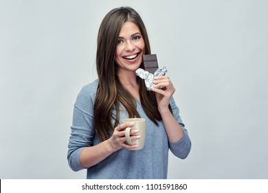 Happy woman eating chokolate and drinking coffee. Isolated studio portrait with copy space.