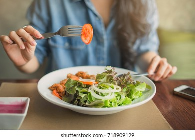 Happy woman eating healthy salad sitting on the table . Beautiful girl eating healthy food.