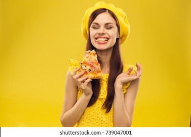 happy woman eating pizza on a yellow background, eating, tasty, sweet