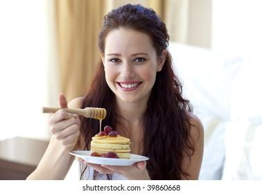 Happy woman eating a sweet dessert in bedroom