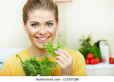 Happy Woman eating  vegetarian food,  standing against  home kitchen interior background. Yellow color clothes. Woman Face close up portrait.