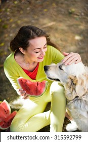 Happy woman eating watermelon with her white dog golden retriever