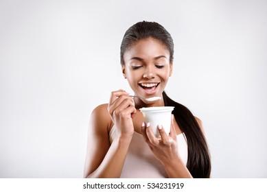 Happy woman is eating yoghurt