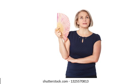 Happy woman emotionally posing in a studio. Middle aged woman is stuffy, hot and she waves a fan, isolated on white background