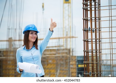Happy woman engineer thumb up at construction site.Copy space