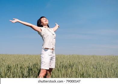 Happy woman enjoy sun on the wheat field