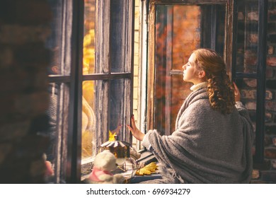 Happy woman enjoying the autumn air at open window