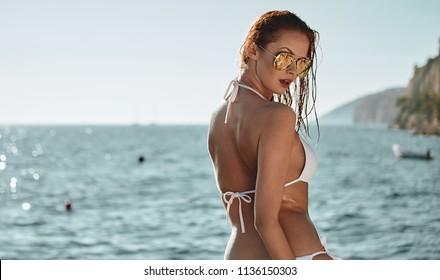 Happy woman enjoying beach relaxing joyful in summer by blue water.