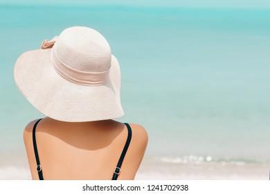 Happy woman enjoying beach relaxing joyful in summer by tropical blue water. Beautiful bikini model happy on travel wearing beach sun hat on beach. Girl on a tropical beach with hat