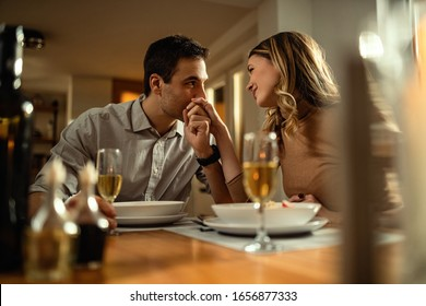 Happy woman enjoying at dining table while being kissed in a hand by her boyfriend.
