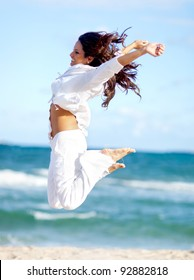 Happy woman enjoying her time at the beach and jumping