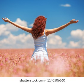 Happy woman enjoying the life in the field with flowers. Nature beauty, blue cloudy sky and colorful field with flowers. Outdoor lifestyle. Freedom concept. Woman in spring summer field