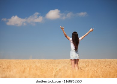 Happy woman enjoying the life in the field Nature beauty, blue cloudy sky and colorful field with golden wheat. Outdoor lifestyle. Freedom concept. Woman in summer field