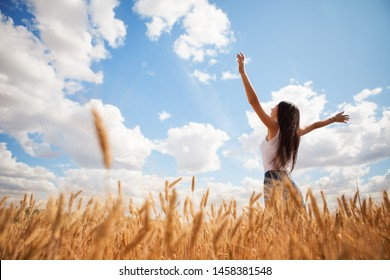 Happy woman enjoying the life in the field. Nature beauty, blue sky,white clouds and field with golden wheat. Outdoor lifestyle. Freedom concept. Woman jump in summer field