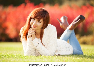 Happy woman enjoying the life in the spring park. Nature beauty, green grass and colorful flowers background. Outdoor lifestyle.