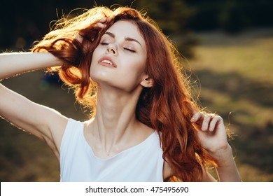Happy woman enjoying nature . Beauty girl in the street. The concept of freedom . Beauty girl over the sky and the sun. Enjoyment