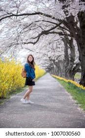 Happy woman enjoying nature. Girl with blooming cherry blossoms sakura tree flowers.