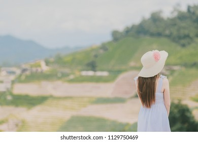 Happy woman enjoying the nature in the mountains and looking on sky with raised hands. Freedom concept