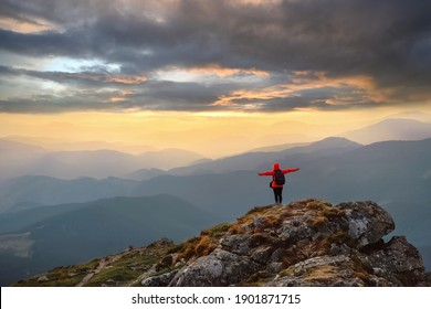 Happy woman enjoying nature in the mountains and looking at sky with raised hands. Freedom concept