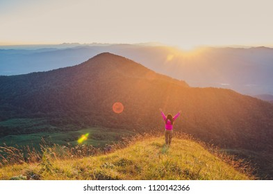 Happy woman enjoying the nature on mountains and looking view with raised hands.