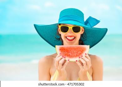 Happy woman enjoying a slice of watermelon on the beach.
