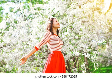 Happy woman enjoying smell flowers over spring garden background