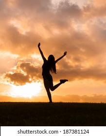Happy woman enjoying the sunset/sunrise. Freedom concept. Enjoyment.