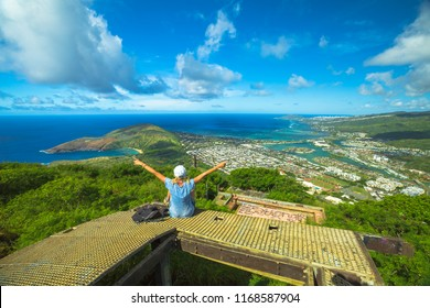 Happy woman enjoying at top of koko head Crater trail.Aerial view of Hanauma Bay, Diamond Head and Honolulu, Oahu, Hawaii, USA. Hawaiian hiking in nature scenic landscape.Female hiker with raised arms
