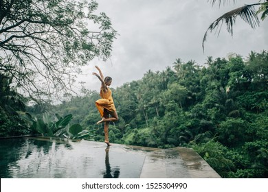 Happy woman enjoying warm tropical rain falling on her on infinity pool with a jungle view in Ubud, Bali