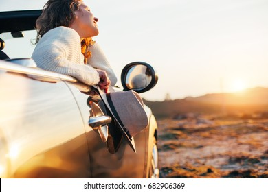Happy woman enjoys a sunset from a convertible