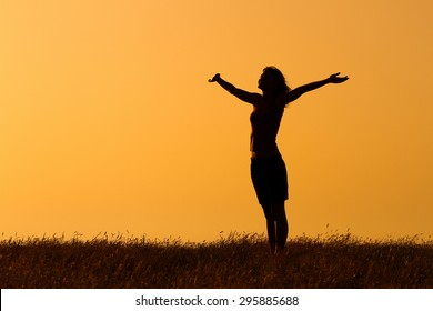 Happy woman enjoys in sunset. Greeting the sunset