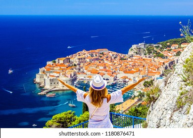 Happy woman enjoys view of old town (medieval Ragusa) and Dalmatian Coast of Adriatic Sea in Dubrovnik. Blue sea with white yachts, beautiful landscape, aerial view, Dubrovnik, Croatia