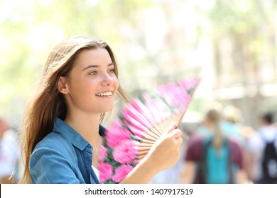 Happy woman fanning walking in the street on summer