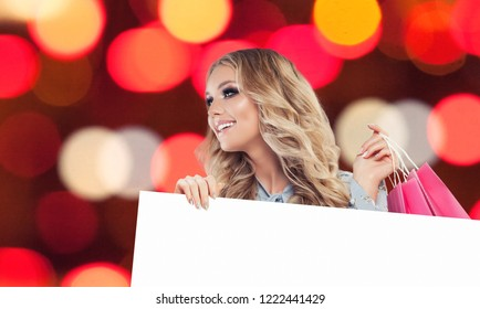 Happy woman fashion model with shopping bag and white paper singboard on celebration bokeh background