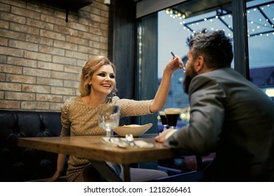 happy woman feed bearded man in cafe. sexy woman and man eating in restaurant